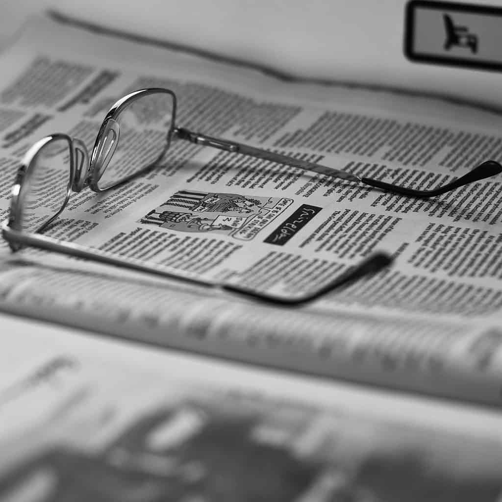 close up of a black and white newspaper with glasses laying ontop of it