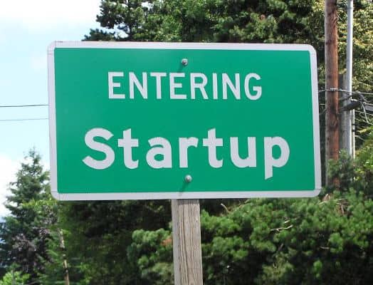 """green and white sign on the side of a road that prints """"entering startup"""""""