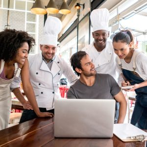 man sitting at a table with a laptop and four restaurant workers standing around him