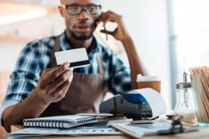 man sitting at a desk on the phone holding up a credit card with paper work at desk