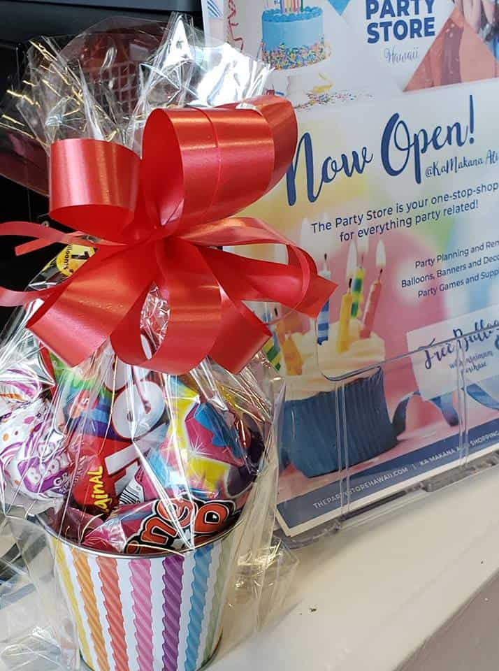 small gift basket with goodies and treats with a red bow on top and a sign next to it that says now open