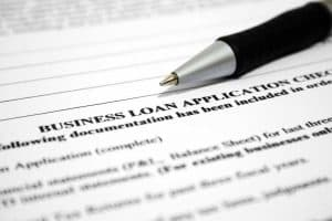 close up of a business loan application with a pen sitting on top of the paper
