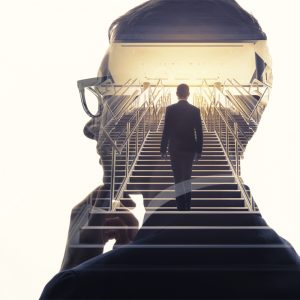 close up on the side of a man thinking with a man walking up stairs in the silhouette of the side profiled man