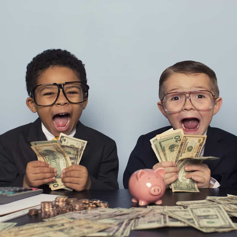 two little boys dressed in buisness suits with money all around them with an excited expression