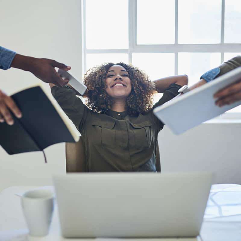 woman leaning back at her desk with arms back, eyes closed, smiling while coworkers are handing things to her