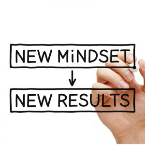 """hand holding a marker as if marker is writing on screen """"new mindset"""" with arrow pointing down """"new results"""""""