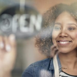 close up of woman employee smiling and flipping over the open sign on a window