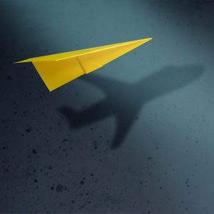 paper airplane with the shadow of an airplane under it