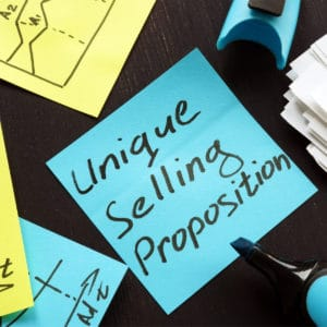 """blue post-it note with marker that prints """"unique selling proposition"""""""