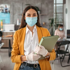 woman in work setting holding binder and wearing a mask