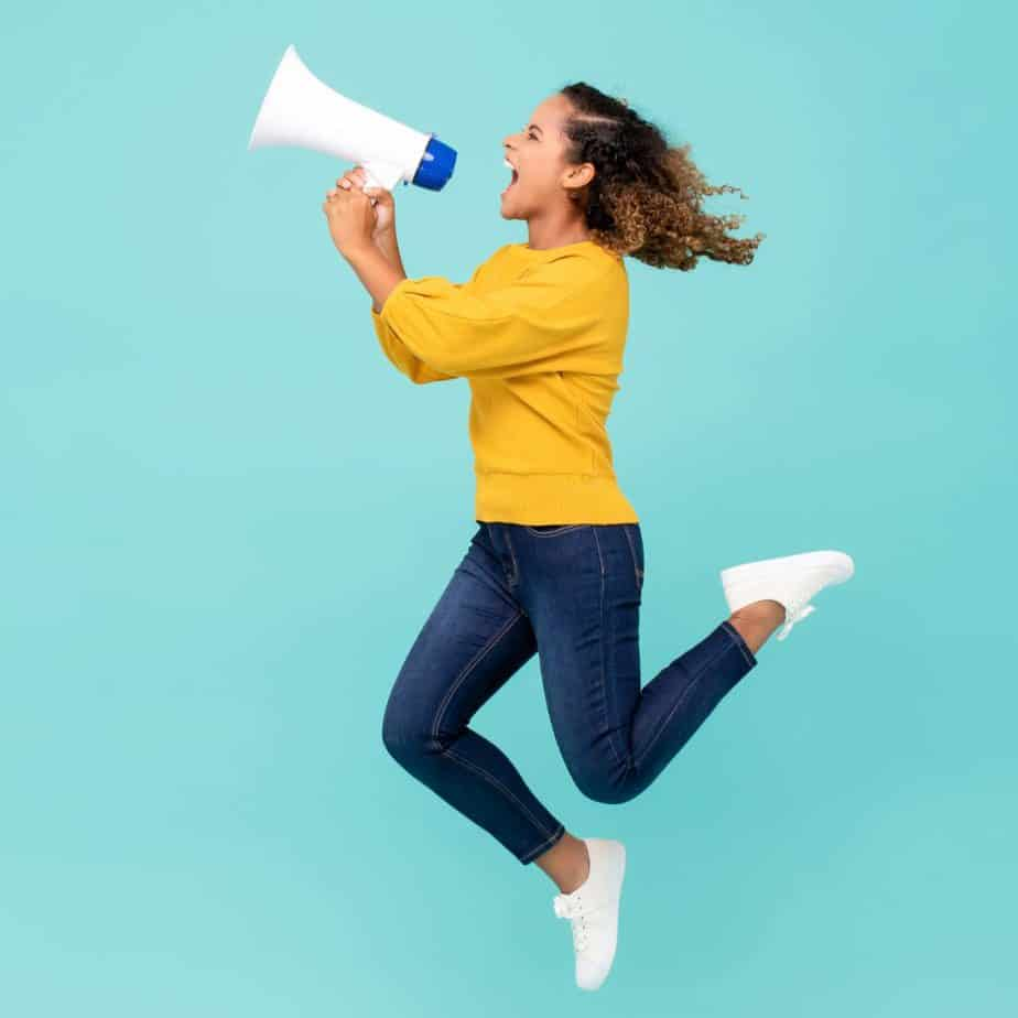 girl jumping up to the side yelling into a megaphone