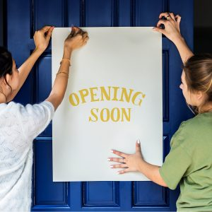 """two women putting up an """"opening soon"""" sign"""