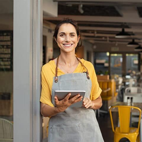 Portrait of happy woman standing at doorway of her store holding digital tablet. Cheerful mature waitress waiting for clients at coffee shop. Successful small business owner in casual clothing and grey apron standing at entrance and looking at camera.